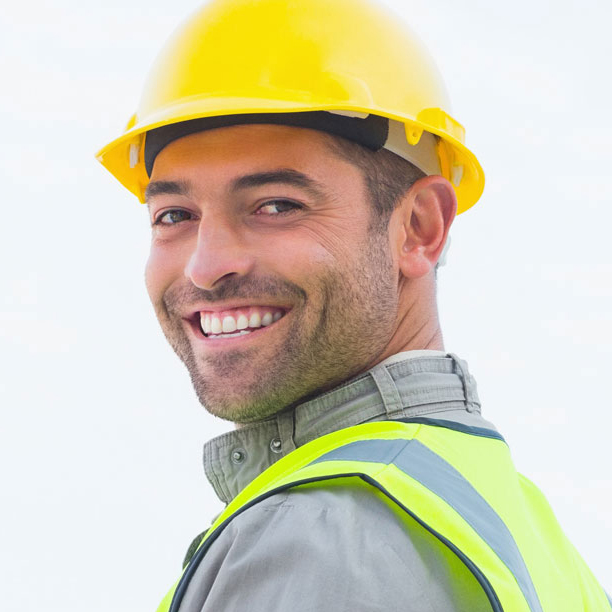 headshot of construction worker smiling while wearing a yellow safety vest and hard hat